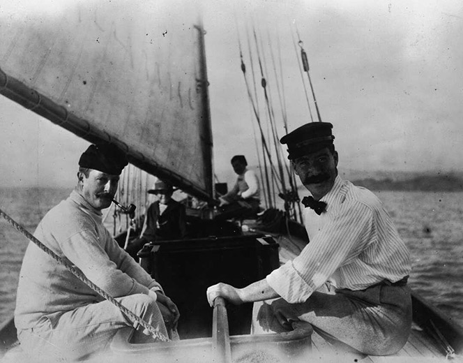 Black and white photo of men on a boat. One of the men is smoking a pipe.