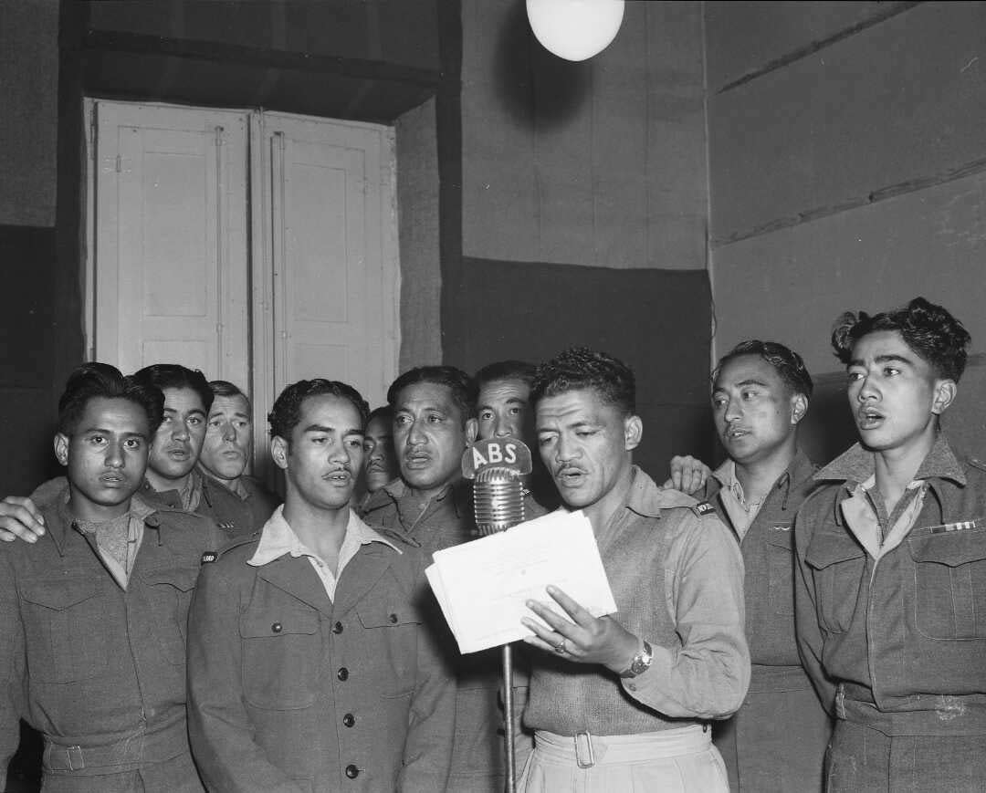 A group of Māori men standing around an old-fashioned microphone singing.