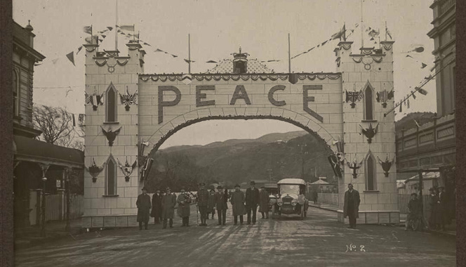Men standing under a large arch across Jackson Street, Petone, displaying the word 'Peace'.