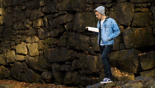 Teen boy wearing jean jacket and hat standing in front of rock wall reading book.
