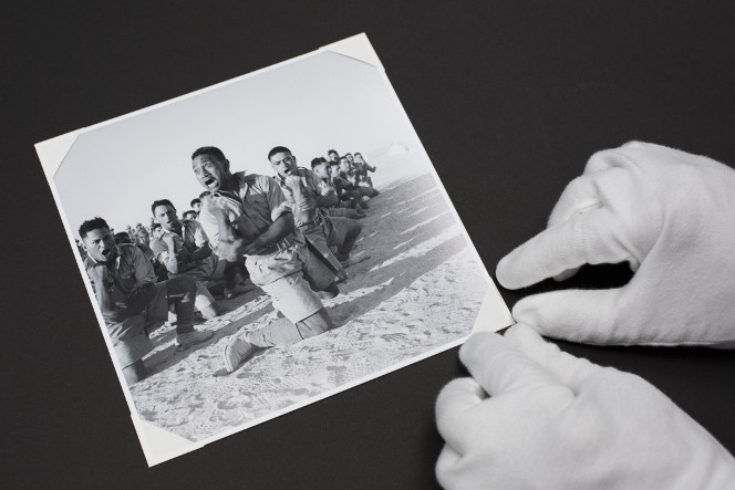 Gloved hands affixing to an album a photo of the Māori Battalion performing a haka, 1941.