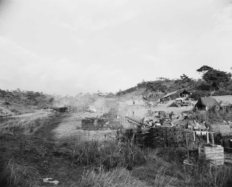 Two large gun emplacements and camp life with jeeps and men drying clothing and making preparations.