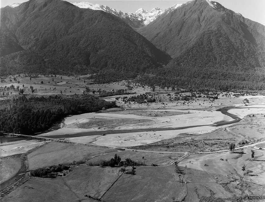 This photograph of Bruce Bay shows the snow-covered southern alps, subalpine forest and the Mahitahi River. Maitahi (Bruce Bay) is where Māui is said to have landed in Aotearoa NewZealand.  [Maitahi](/files/schools/hm38-maitahi-english.mp3)