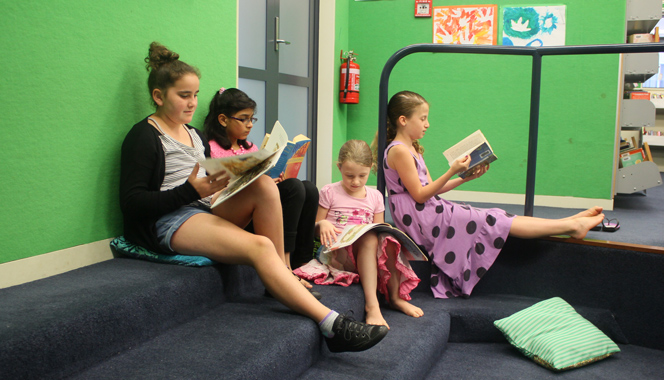 Children reading during a class session at a school library.