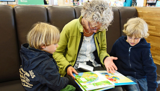 Grandmother reading a book to two young boys
