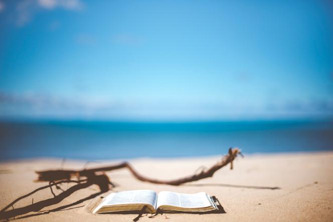 An open book on a sunny sandy beach.