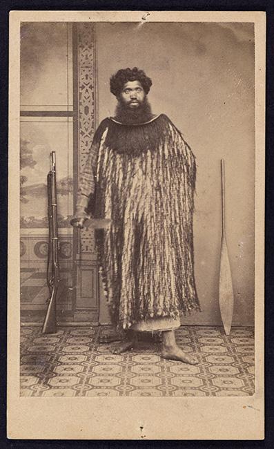 Portrait of Hetaraka Tautahi, 1860–1880. Tautahi wears a long korowai (flax fibre cloak with tassles) over a checked shirt. He holds a mere pounamu and placed beside him are a rifle and a hoe (paddle).  [Portrait of Hetaraka Tautahi](/files/schools/hm06-portrait-of-hetaraka-tautahi-english.mp3)