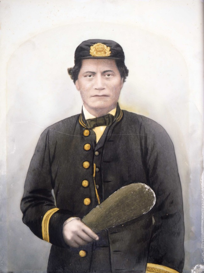 Waist-length portrait of a Maori man, identified as Rawiri Puaha, with moko, dressed in uniform, including cap, holding a mere in his right hand.