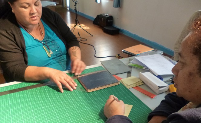 Mary Bercich and Evelyn Barber measuring their book before making their four-flap folder.
