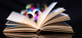 Open books with 2 pages shaped in a heart with brightly coloured circles around it.