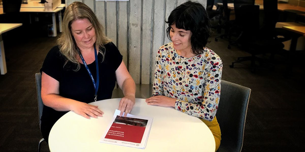 Services to School staff member looking at the School Library Development Framework document with a teacher seated at a table