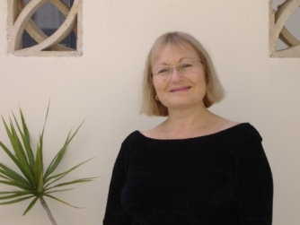 Shows Edna Shemesh standing against a white wall.