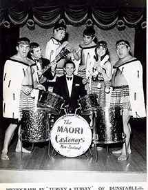 Māori performers standing around a drum kit.