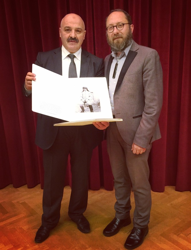 Corin Haines presents a photographic print from the Alexander Turnbull Library to a representative from the National Library of Turkey.