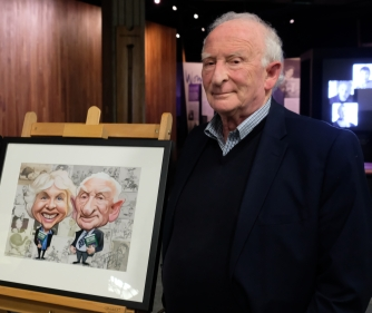 Ian Grant with a framed caricature of himself and his wife.