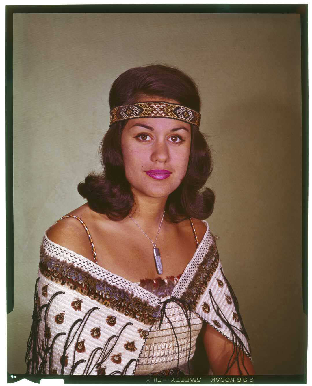 Portrait of a woman with a Māori cloak and headband.
