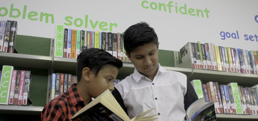 Two boys reading in their school library.