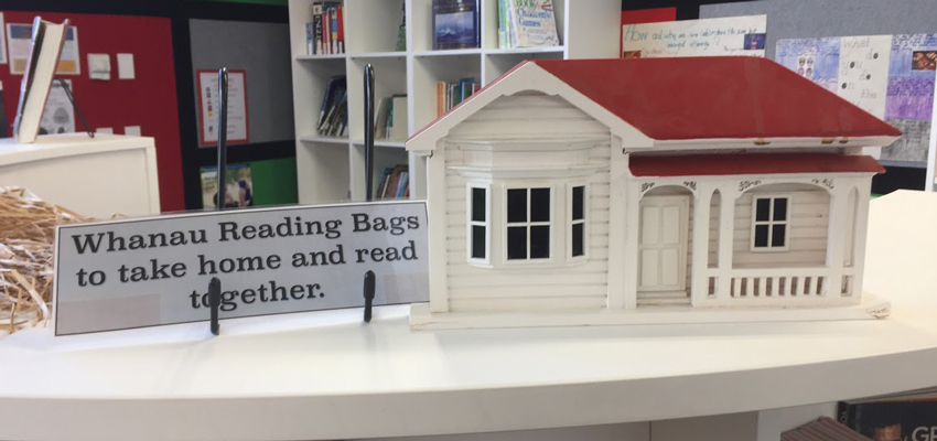 Shelf-topper — model of villa house with sign 'Whanau Reading Bags to take home and read together'
