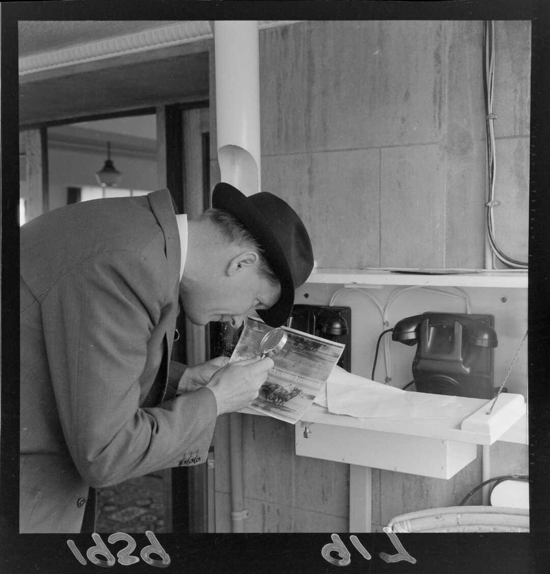 Unidentified man inspecting a photo finish record with a magnifying glass