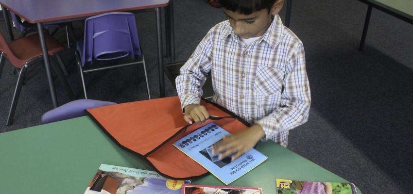 A boy filling up his bag with books to read at home