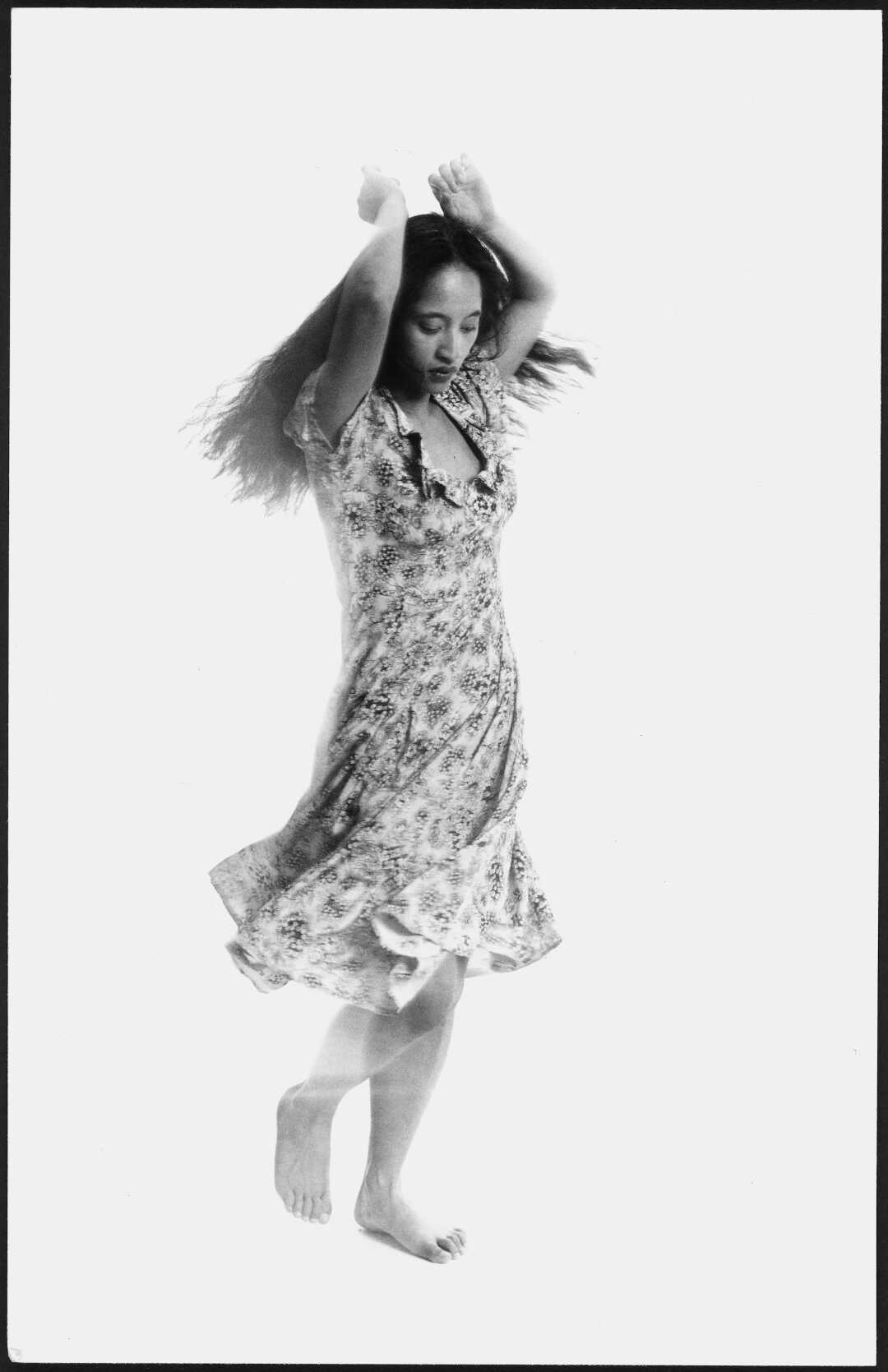 A woman with her arms above her head dancing. Her dress is swooshing around her.