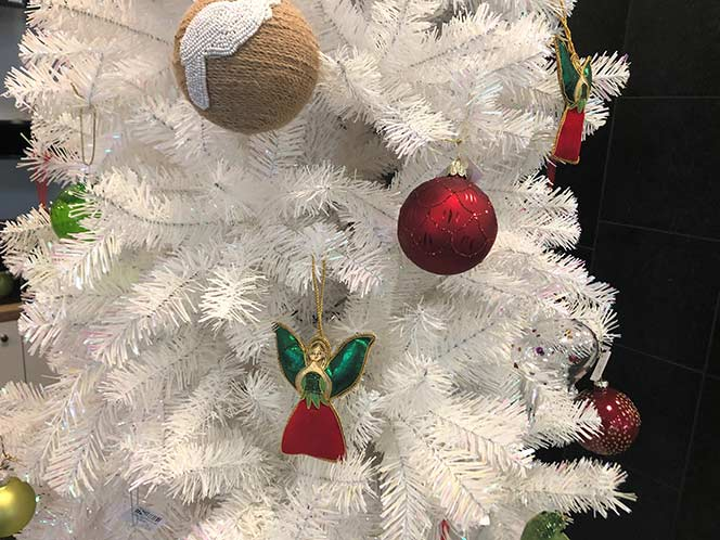 Detail of a white Christmas tree with decorations.