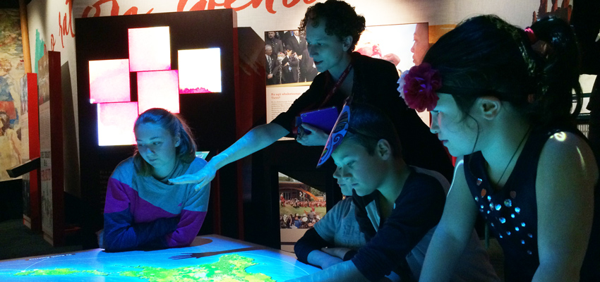 School children with a Learning Facilitator gathered around a display table at the He Tohu exhibition in Wellington