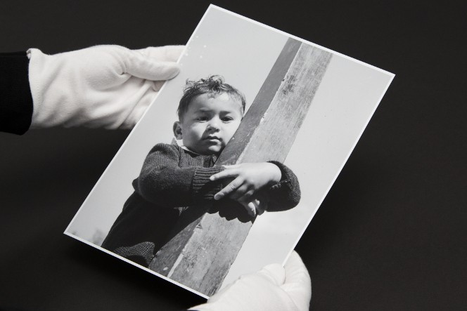 Gloved hands holding a photograph of a young Māori boy