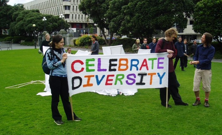 Two people standing on the green grass of Parliament grounds holding a large colourful sign that reads: Celebrate Diversity .