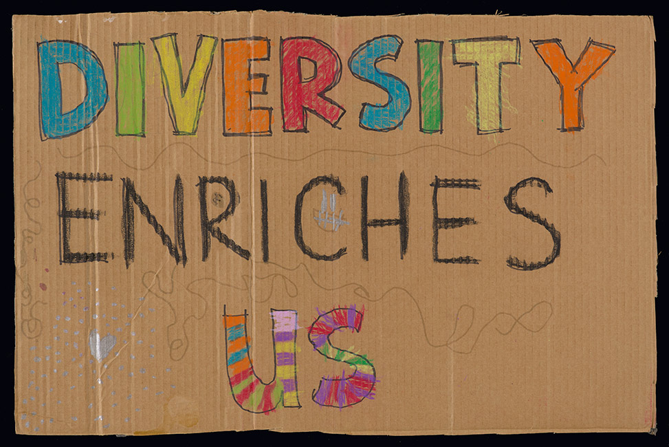 This placard was carried on the 'Women's March on Washington' in Wellington on 21 January 2017 from Parliament to Civic Square. It reads, 'Diversity Enriches Us'. The placard is hand drawn on corrugated cardboard and the words 'Diversity' and 'Us' are multi-coloured.  [Diversity](/files/schools/hm64-diversity-english.mp3)