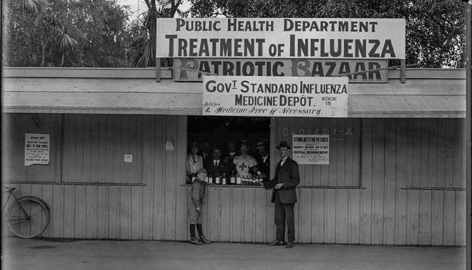 2 people standing outside influenza medicine depot. Signs on roof read 'Public Health Department Treatment of Influenza' and 'Govt Standard Influenza Medicine Depot'.