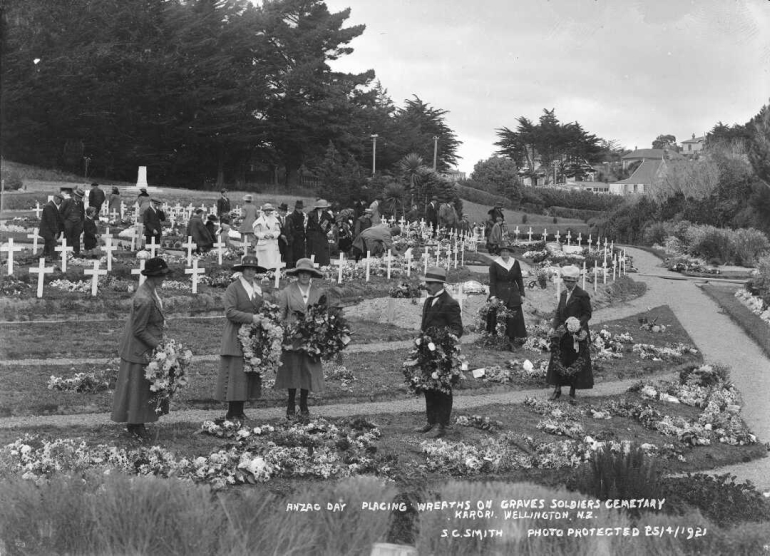 Men and women placing wreaths on the ground where graves are marked at Karori cemetery.