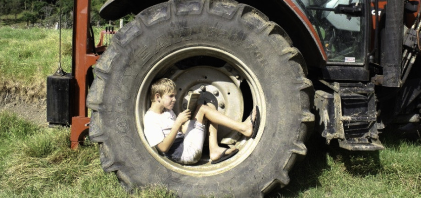 Boy in tractor wheel doing summer reading.