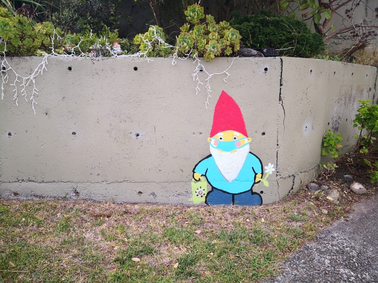 Colourful gnome wearing a mask painted on a concrete wall.