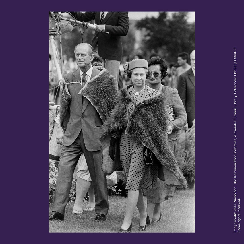 Front of curiosity card TMCC12 with an image of Queen Elizabeth and the Duke of Edinburgh wearing kahu kiwi (cloaks made with kiwi feathers)