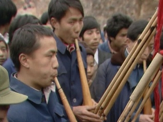 Stills from a documentary titled 'Big Nose', featuring individuals playing a lusheng: a six-piped bamboo mouth organ.
