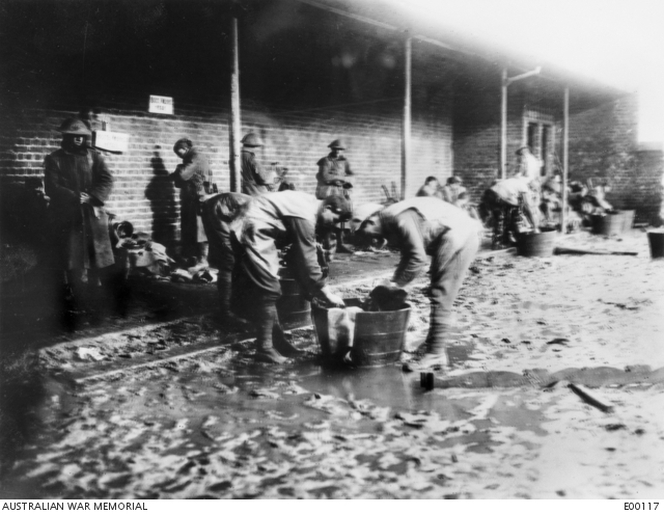 Informal photograph of members of the 42nd Battalion, just out of the line, washing the mud off their gumboots. Armentieres, January 1917. Australian War Memorial.
