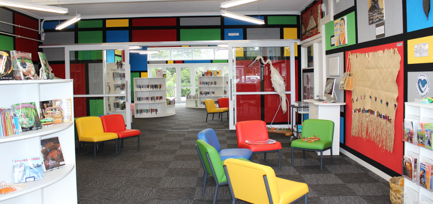 Colourful school library with chairs and bookshelves.