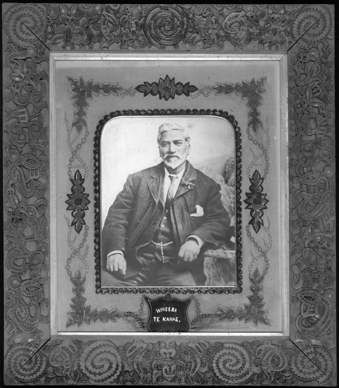 Portrait of Wineera Te Kanae, seated wearing a european suit. He appears to be about 50 years of age. The portrait is surrounded with a decorated mat board and well carved picture frame. The frame was carved by Piwiki Horohau, of Ngati Raukawa and Ngati Toa descent, about the time he carved the meeting house Toa Rangatira (ca 1900).