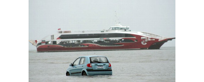 It's a car, in the water, with a big boat in the background. The boat is supposed to be in the water. The car is not.
