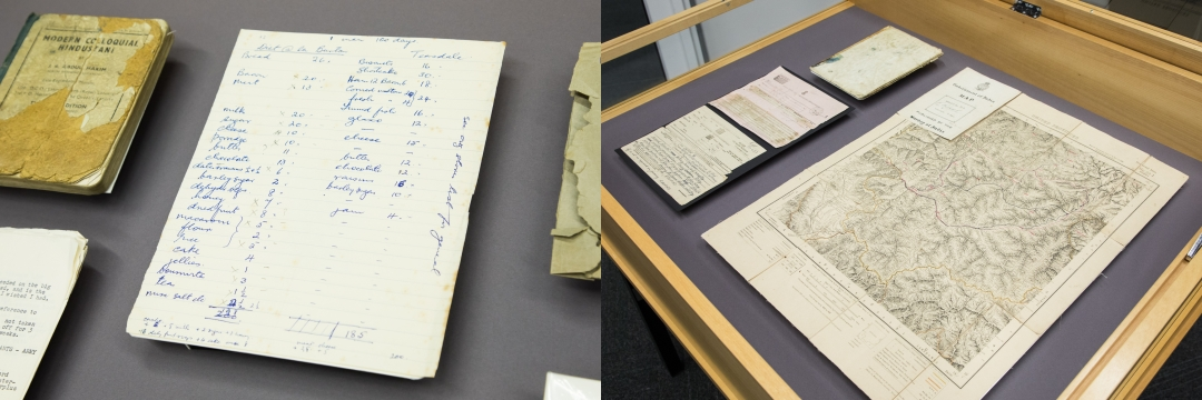 Collection items in a display case, including a map and papers.