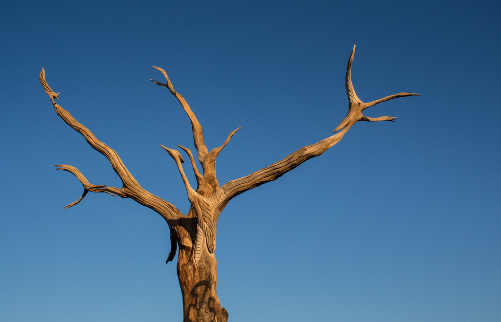 A sculpture of a tree with no leaves against a blue sky.