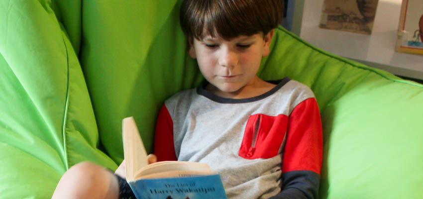Boy enjoying reading in a beanbag.