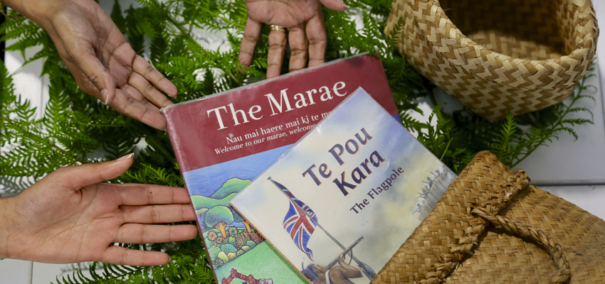 Shows two Maori themed books, two kete and three outstretched hands.