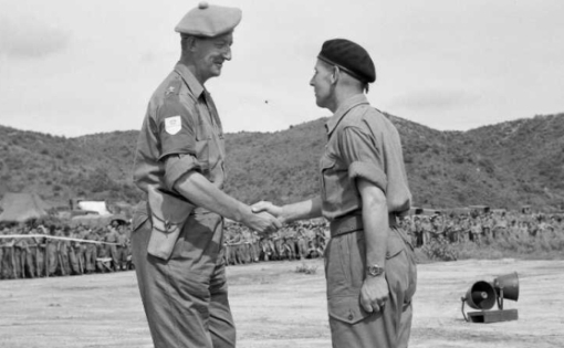 Two men in military dress shaking hands in front of a crowd of fellow soldiers.