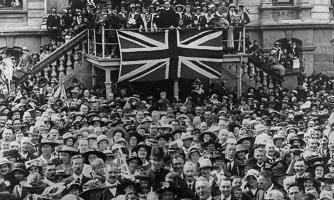 Armistice Day crowd celebrating in Dunedin with Union Jack flag.