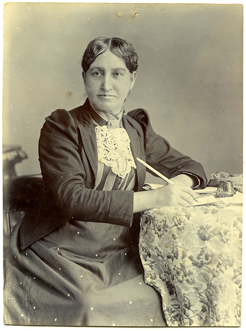 Elizabeth Yates, first woman in the British Empire to hold the office of mayor (Onehunga), 1894. This photograph shows her sitting at a cloth covered table with a pen, poised to write.  [Elizabeth Yates](/files/schools/hm40-elizabeth-yates-english.mp3)