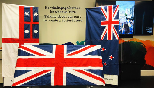 3 flags of Aotearoa New Zealand displayed in the He Tohu Tāmaki exhibition space in front of words: 'He whakapapa kōrero he whenua kura. Talking about our past to create a better future'.