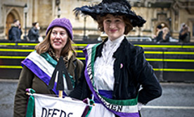 Two women, one dressed as a suffragette, wearing sashes with words 'Votes for women' and holding a banner 'Deeds not words'.
