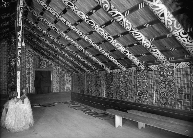 Interior view of Hinenuitepo meeting house at Te Whaiti. There are streamers across the ceiling, and photographs all along the walls.